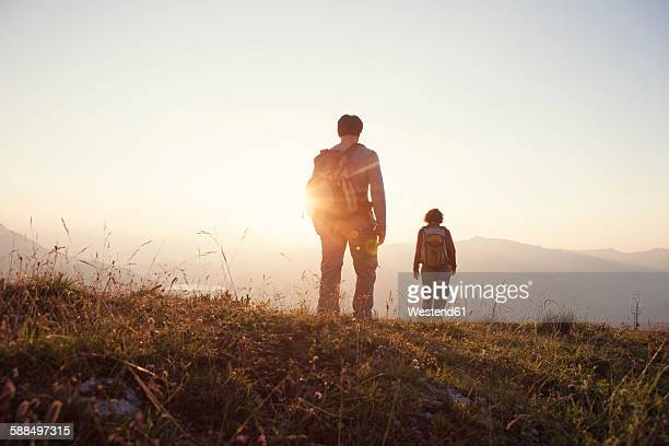 Austria, Tyrol, couple hiking at Unterberghorn at sunset
