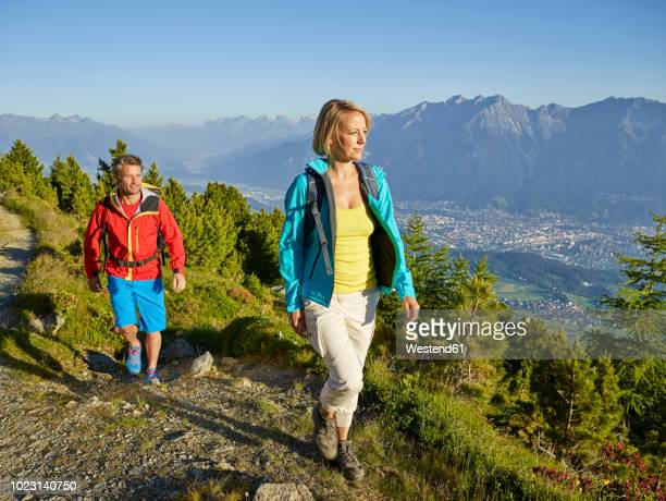austria, tyrol, couple hiking the zirbenweg at the patscherkofel - buitensport stockfoto's en -beelden