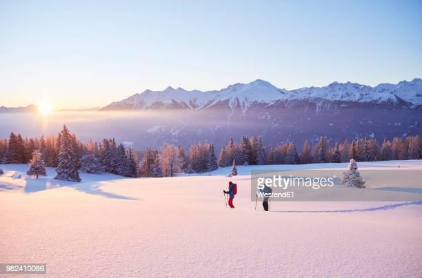 austria, tyrol, couple snowshoeing at sunrise - alpes europeos fotografías e imágenes de stock