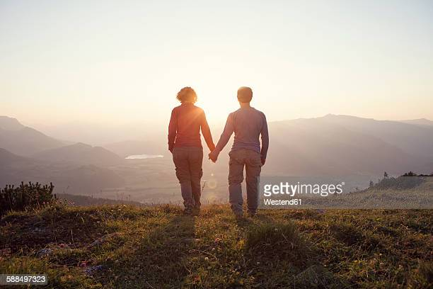 Austria, Tyrol, couple walking hand in hand at Unterberghorn at sunset
