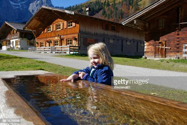 Austria, Tyrol, Eng, small girl bathing hand in drinking trough