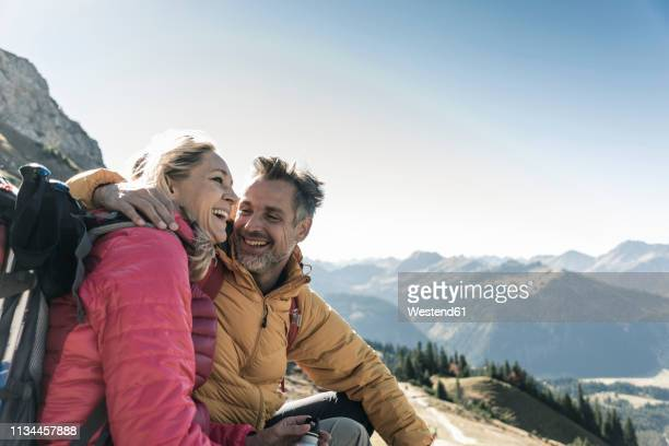 austria, tyrol, happy couple having a break during a hiking trip in the mountains - 40 49 jaar stockfoto's en -beelden