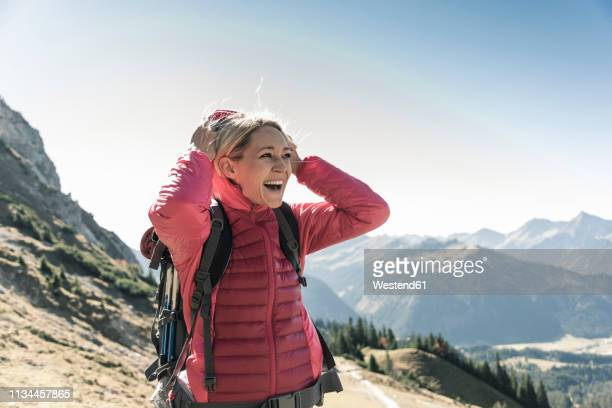 austria, tyrol, happy woman on a hiking trip in the mountains enjoying the view - jacke stock-fotos und bilder