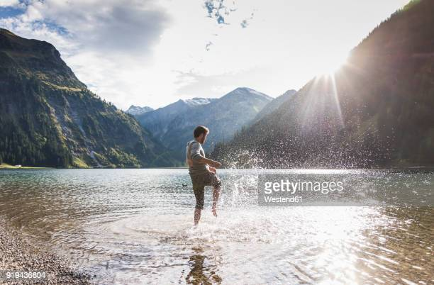 Austria, Tyrol, hiker splashing in mountain lake