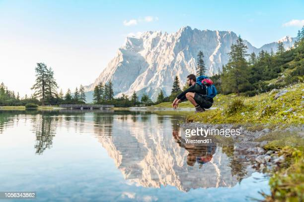 austria, tyrol, hiker taking a break, crouching by the lake - autriche photos et images de collection
