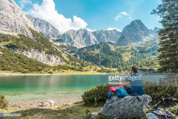 austria, tyrol, hiker taking a break, sitting on a rock, looking at lake - österreich stock-fotos und bilder