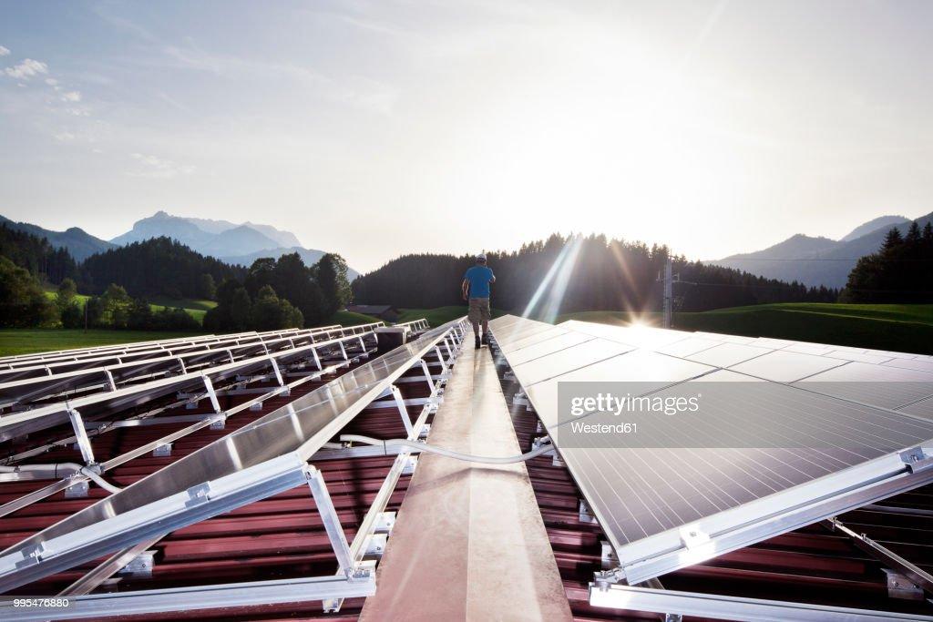 Austria, Tyrol, Koessen, back view of worker walking on solar plant in the evening : Stock-Foto