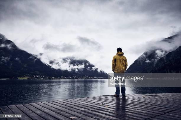 austria, tyrol, lake achen, man standing on boardwalk - bedeckter himmel stock-fotos und bilder