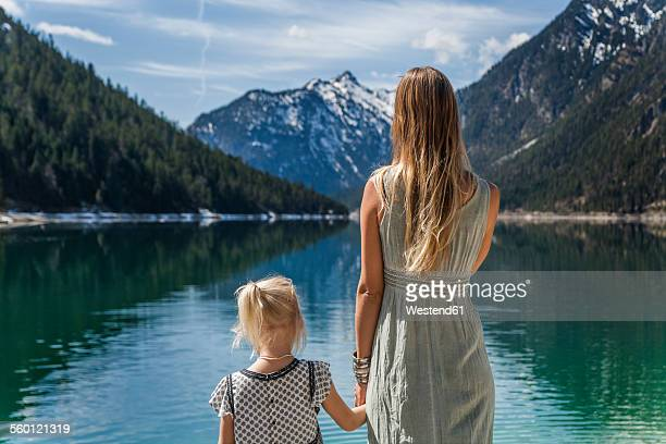 Austria, Tyrol, Lake Plansee, mother and daughter at lakeshore