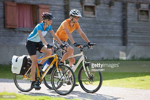 Austria, Tyrol, Man and woman cycling through road