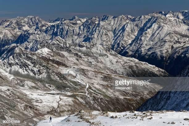 Austria, Tyrol, Oetztal, Soelden, woman in snowcapped landscape with view on Oetztal Glacier Road