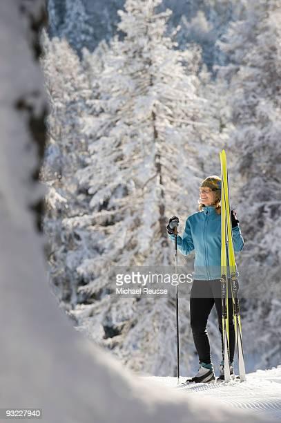 Austria, Tyrol, Seefeld, Wildmoosalm, Woman holding cross-country skis