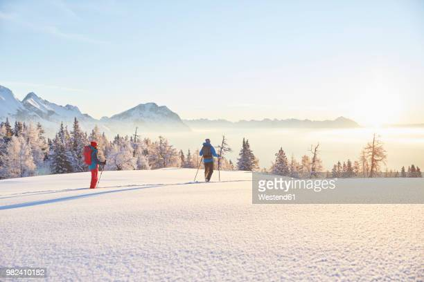 austria, tyrol, snowshoe hikers at sunrise - wintersport stock-fotos und bilder