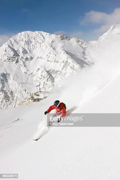Austria, Tyrol, Stubaital, man skiing downhill, elevated view