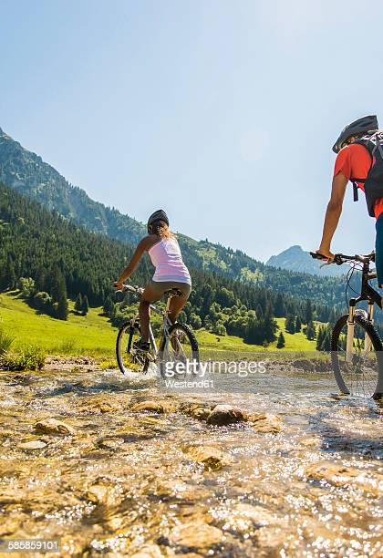 Austria, Tyrol, Tannheim Valley, young couple on mountain bikes crossing brook