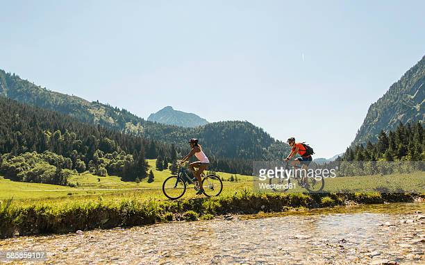 Austria, Tyrol, Tannheim Valley, young couple riding mountain bike at riverside