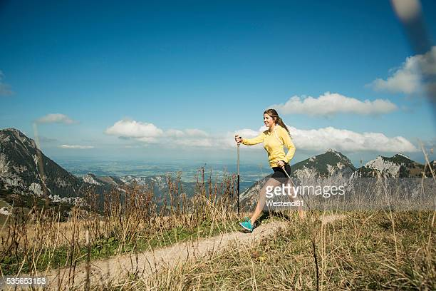 Austria, Tyrol, Tannheim Valley, young woman nordic walking in mountains