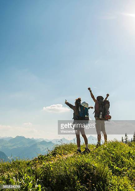 Austria, Tyrol, Tannheimer Tal, cheering young couple standing on mountain trail looking at view