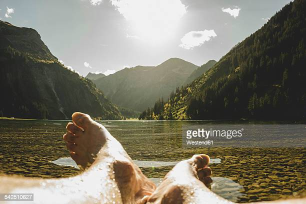 austria, tyrol, tannheimer tal, feet of a man at lakeshore - mujeres fotos stock pictures, royalty-free photos & images