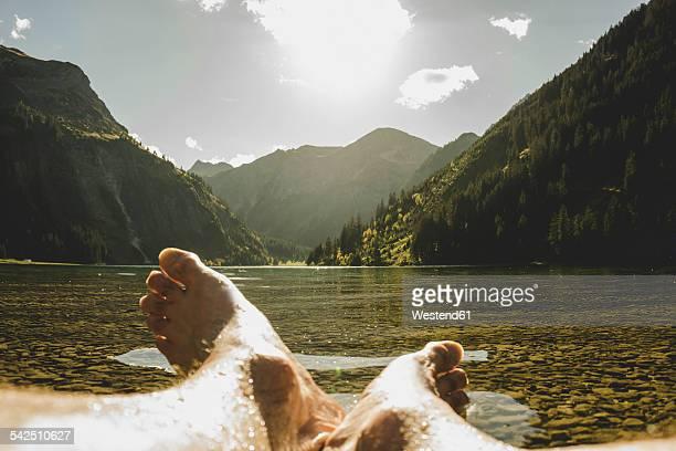 Austria, Tyrol, Tannheimer Tal, feet of a man at lakeshore
