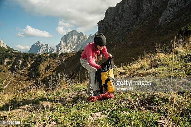 Austria, Tyrol, Tannheimer Tal, female hiker with backpack on alpine meadow