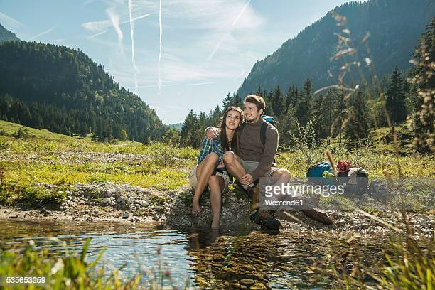 Austria, Tyrol, Tannheimer Tal, two happy young hikers relaxing