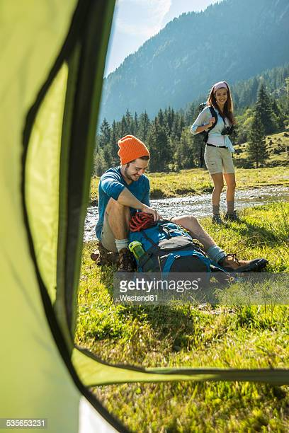 Austria, Tyrol, Tannheimer Tal, two young hikers relaxing