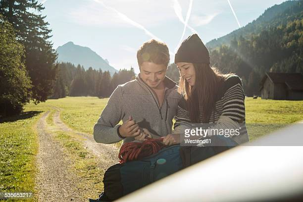 Austria, Tyrol, Tannheimer Tal, two young hikers with rope and backpack
