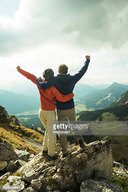 Austria, Tyrol, Tannheimer Tal, young couple cheering on mountain top