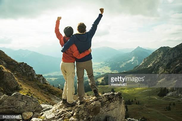 austria, tyrol, tannheimer tal, young couple cheering on mountain top - arme hoch stock-fotos und bilder