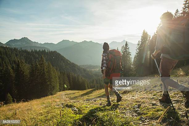 Austria, Tyrol, Tannheimer Tal, young couple hiking in sunlight on alpine meadow