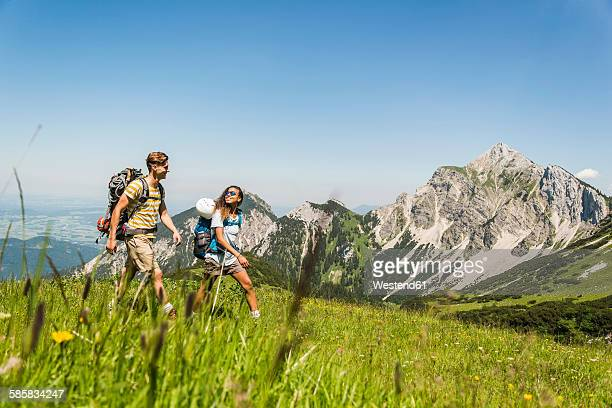 Austria, Tyrol, Tannheimer Tal, young couple hiking on alpine meadow