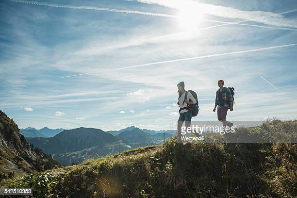 Austria, Tyrol, Tannheimer Tal, young couple hiking on mountain trail