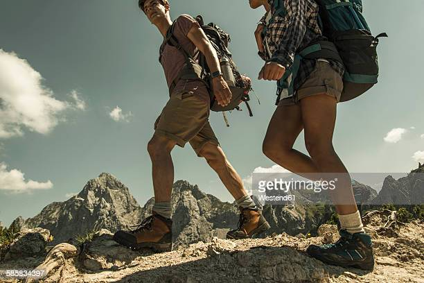 Austria, Tyrol, Tannheimer Tal, young couple hiking on mountain trail