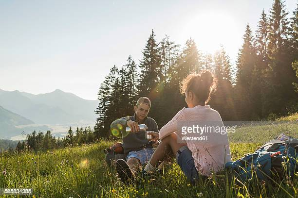 Austria, Tyrol, Tannheimer Tal, young couple resting on alpine meadow