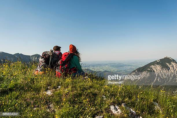 Austria, Tyrol, Tannheimer Tal, young couple sitting on alpine meadow looking at view