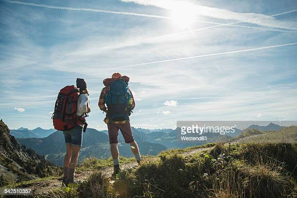 Austria, Tyrol, Tannheimer Tal, young couple standing on mountain trail
