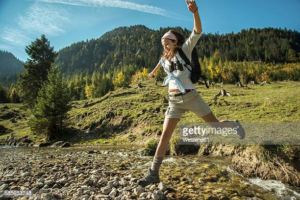 Austria, Tyrol, Tannheimer Tal, young female hiker crossing water