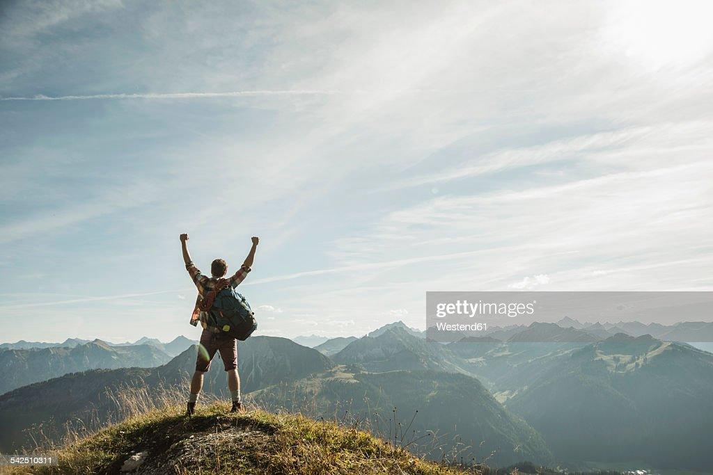 Austria, Tyrol, Tannheimer Tal, young man cheering on mountain top : Stock-Foto
