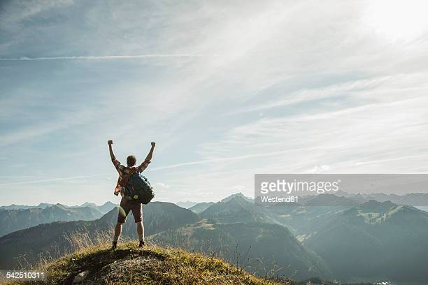 austria, tyrol, tannheimer tal, young man cheering on mountain top - mountain peak stock pictures, royalty-free photos & images