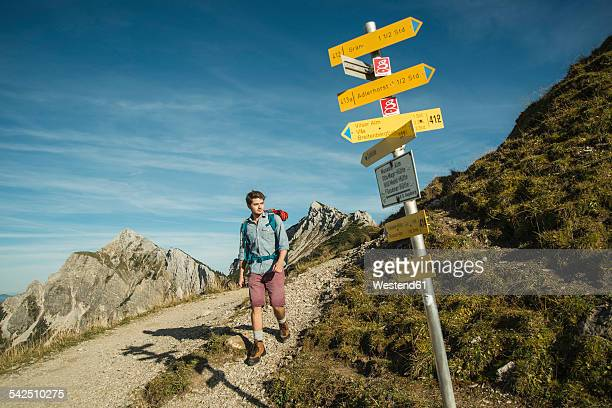 Austria, Tyrol, Tannheimer Tal, young man hiking on mountain trail