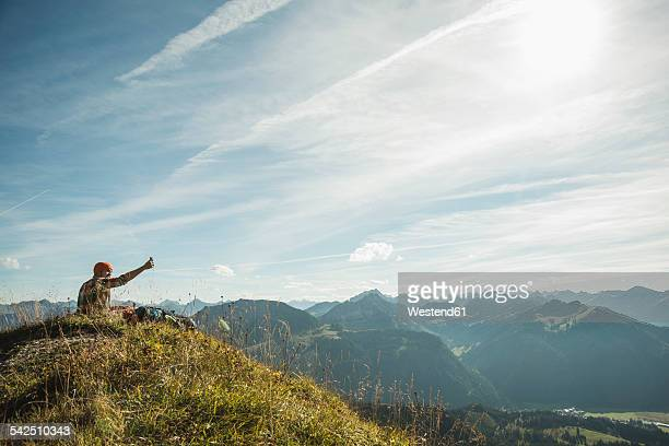 Austria, Tyrol, Tannheimer Tal, young man taking selfie in mountainscape