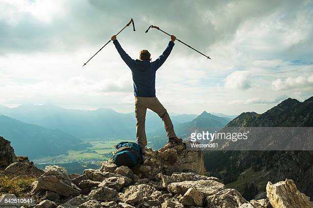 Austria, Tyrol, Tannheimer Tal, young man with hiking poles cheering on mountain top
