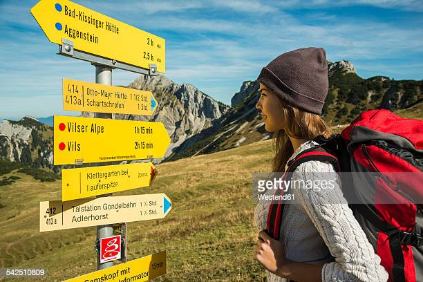 Austria, Tyrol, Tannheimer Tal, young woman on hiking trip at signpost