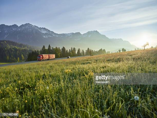 austria, tyrol, truck on country road in the morning light - lkw stock-fotos und bilder