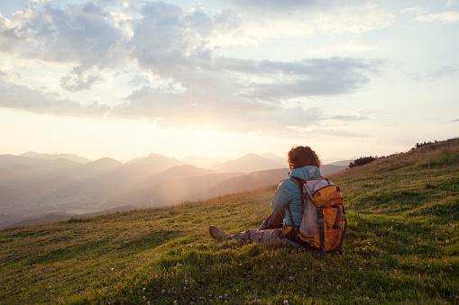 Austria, Tyrol, Unterberghorn, hiker resting in alpine landscape at sunrise - gettyimageskorea