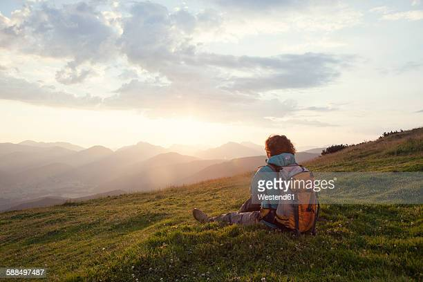 Austria, Tyrol, Unterberghorn, hiker resting in alpine landscape at sunrise