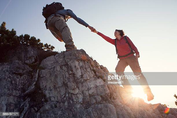 Austria, Tyrol, Unterberghorn, man helping woman on hiking trip
