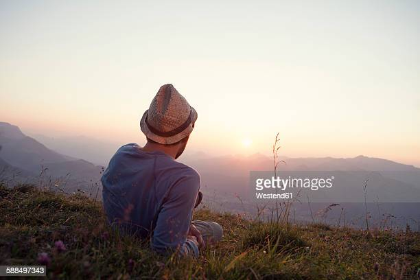 Austria, Tyrol, Unterberghorn, man resting on alpine meadow at sunset