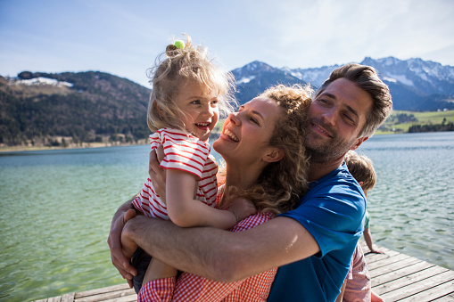 Austria, Tyrol, Walchsee, happy family hugging on a jetty at the lakeside - gettyimageskorea